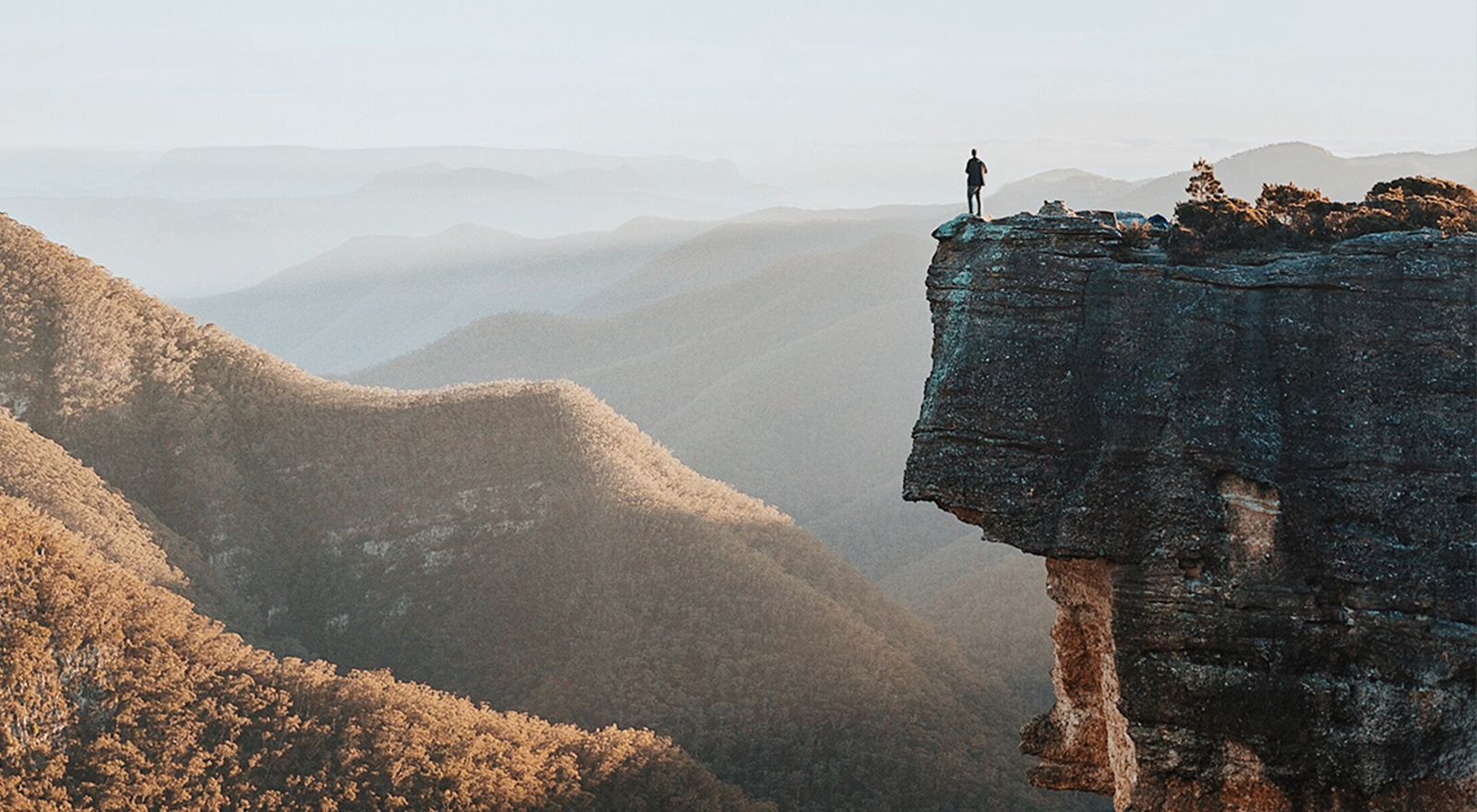 man standing at edge of cliff